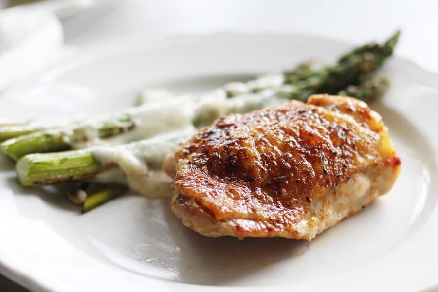 A shot of a piece of chicken served with roasted asparagus.