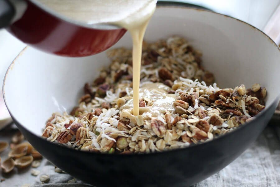 A mixture of melted butter, honey and brown sugar being poured over granola ingredients in a bowl