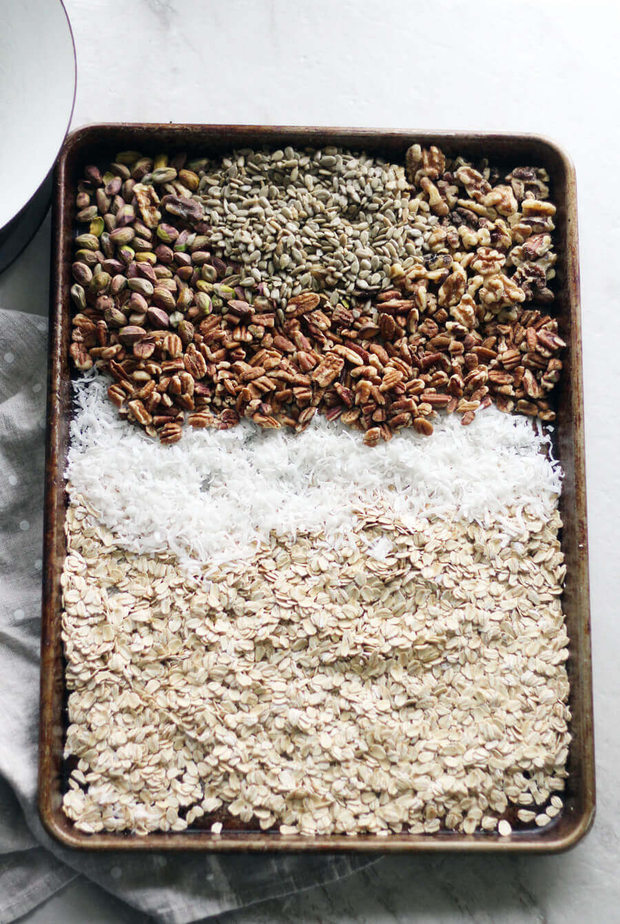 A baking sheet of oatmeal, coconut, pecans and pistachios