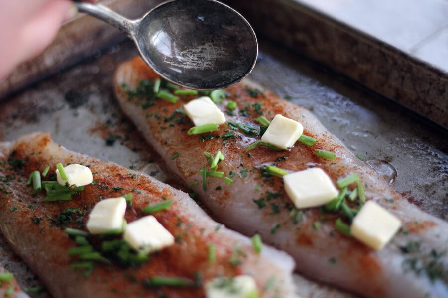 Catfish fillets topped with paprika, parsley and chives and pats of butter