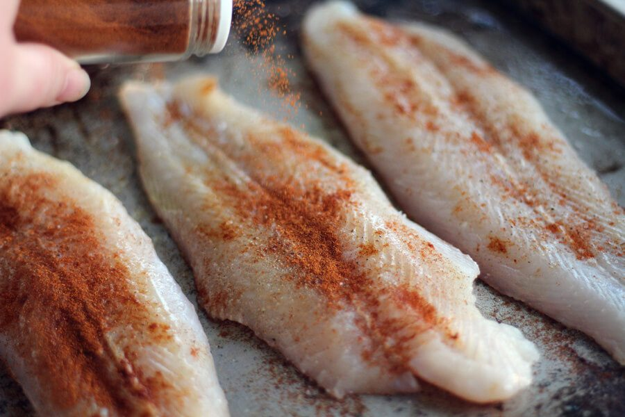 Fresh catfish fillets on a baking sheet being