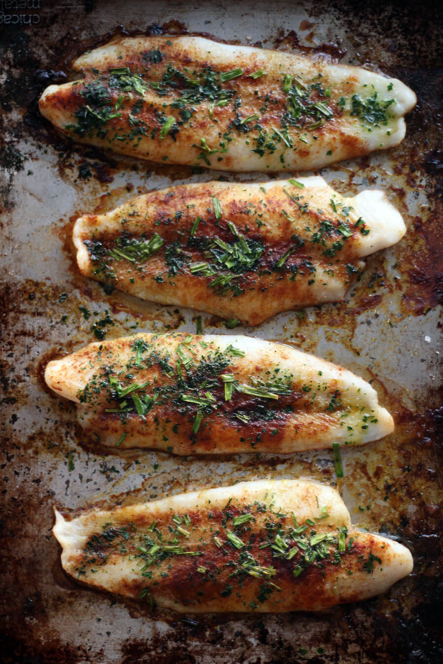 A baking sheet of baked catfish, seasoned with paprika, fresh parsley and chives