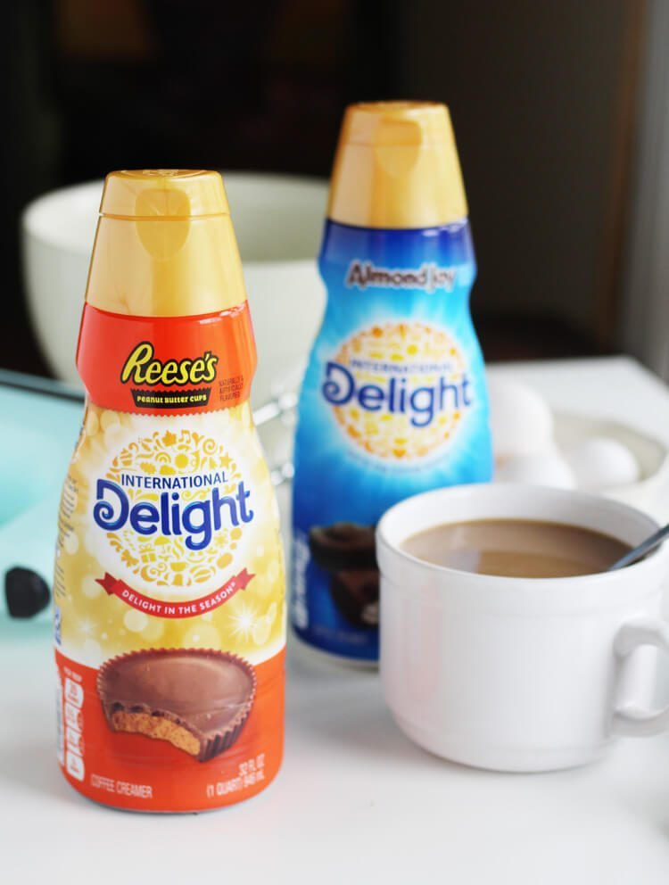 International Delight Reese's Peanut Butter cup coffee creamer, Almond Joy coffee creamer, and a cup of coffee