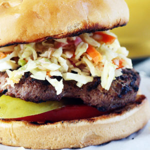 A juicy grilled hamburger with tomatoes, pickles and topped with sweet + tangy cabbage slaw.