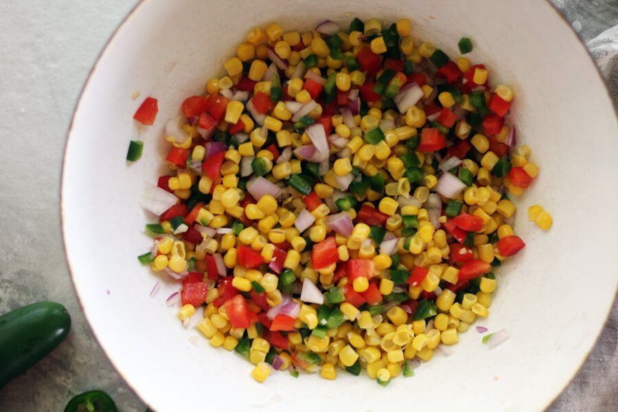 Overhead shot of corn, chopped jalapeños and vegetables in a bowl
