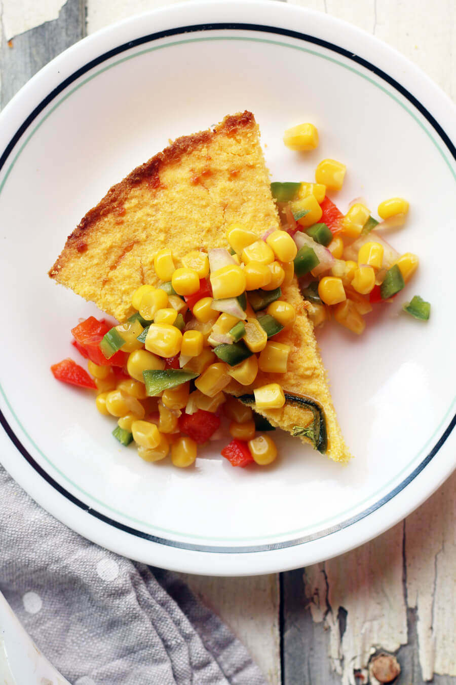 Corn relish served over a wedge of golden cornbread