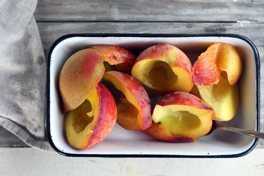 a metal bowl filled with fresh peaches