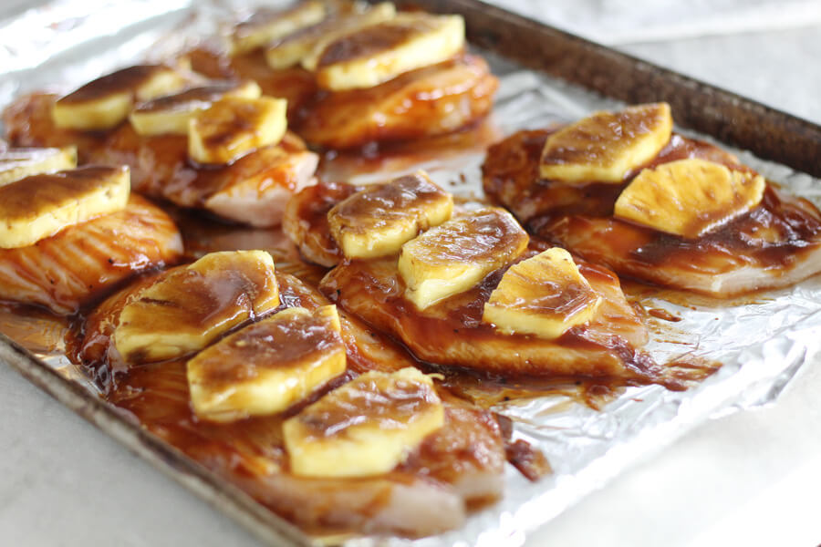 a pan of 6 chicken cutlets, each topped with barbecue sauce and pineapple slices