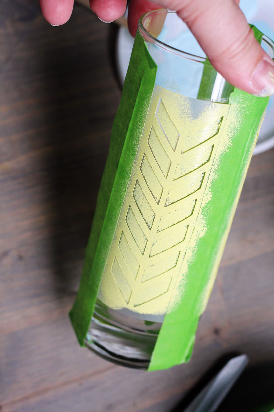 a picture of a high ball cocktail glass with stencil taped to it with yellow paint