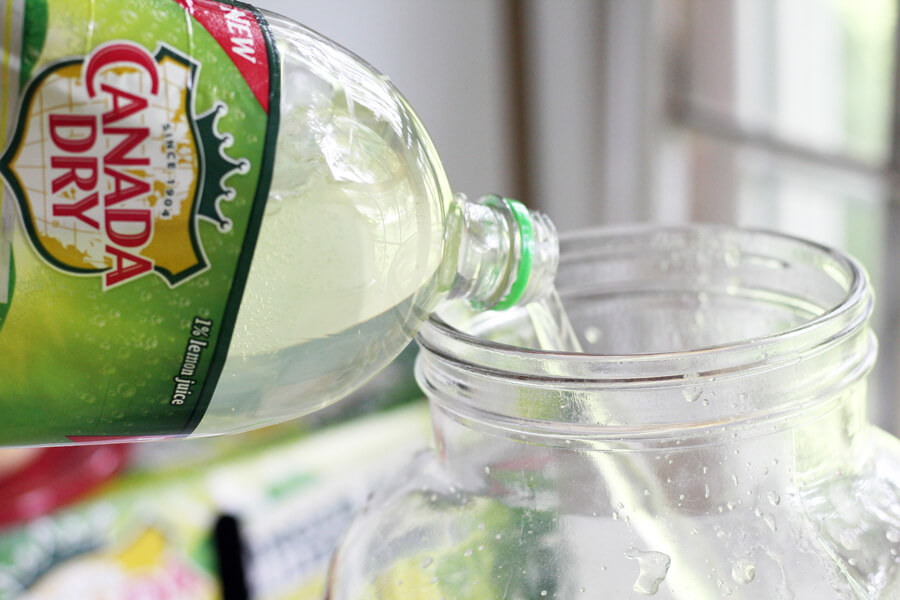 A two liter of carbonated ginger ale being poured into a glass pitcher