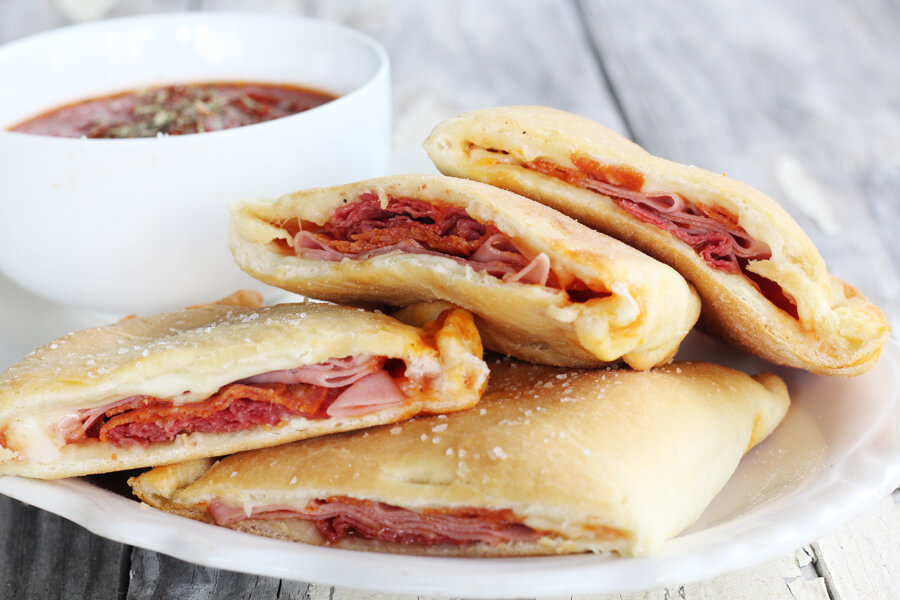 Pizza calzones sliced in half with ham, beef and pepperoni