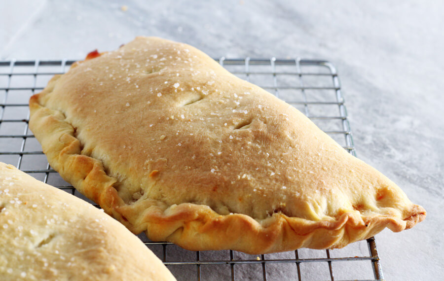 A close up shot of a golden brown pizza calzone cooling on a wire rack