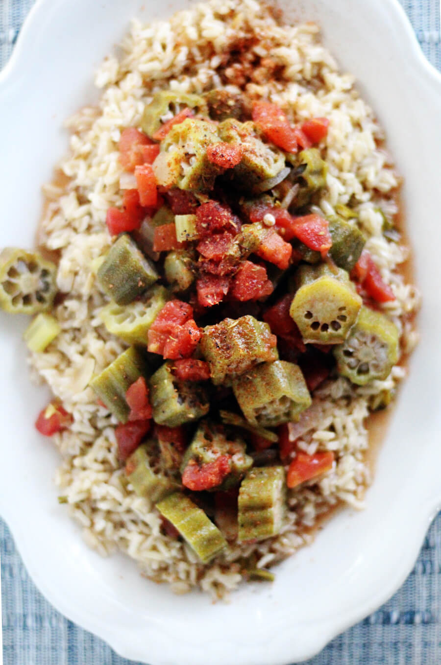 an overhead shot of a white platter of white rice with stewed okra and tomatoes on top