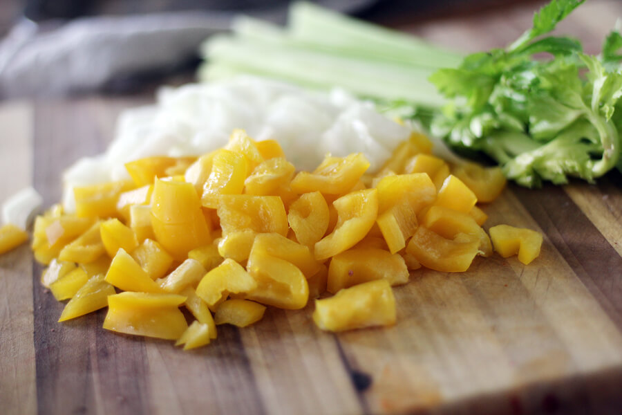 a cutting board with chopped yellow bell peppers, celery and onions