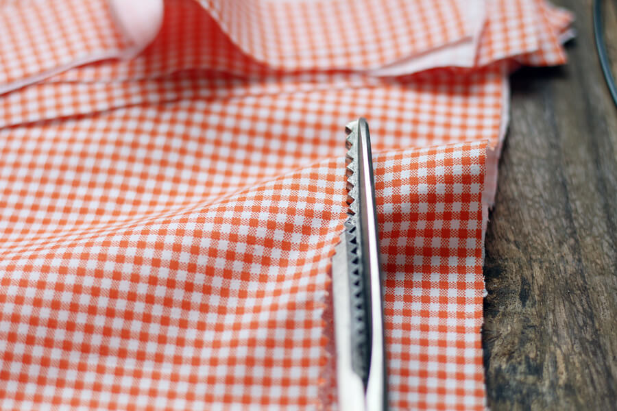 a picture of orange gingham fabric being cut with pinking shears