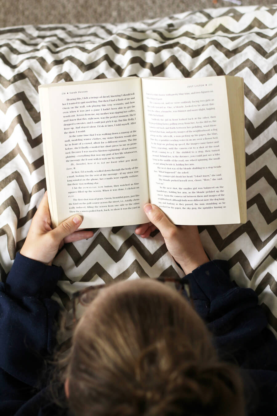 an overhead picture of a young girl reading a book