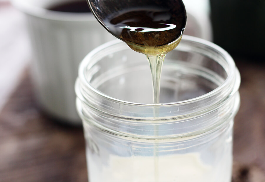 sweet honey being drizzled into a jar of whole milk