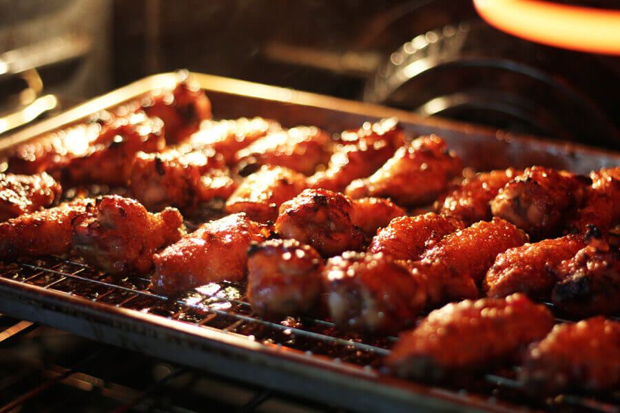 chicken wings broiling in an oven