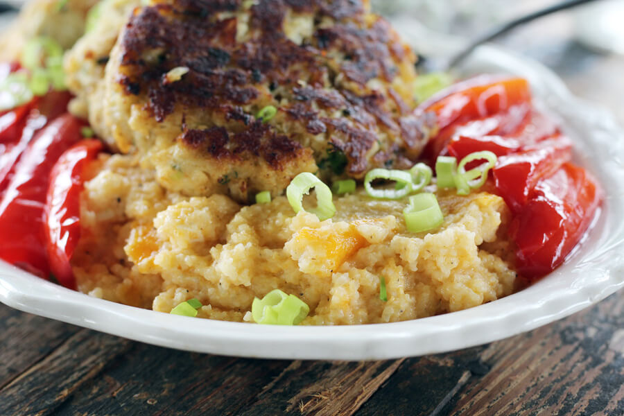 A platter of savory cheese grits served with roasted red bell peppers and topped with butter seared crab cakes
