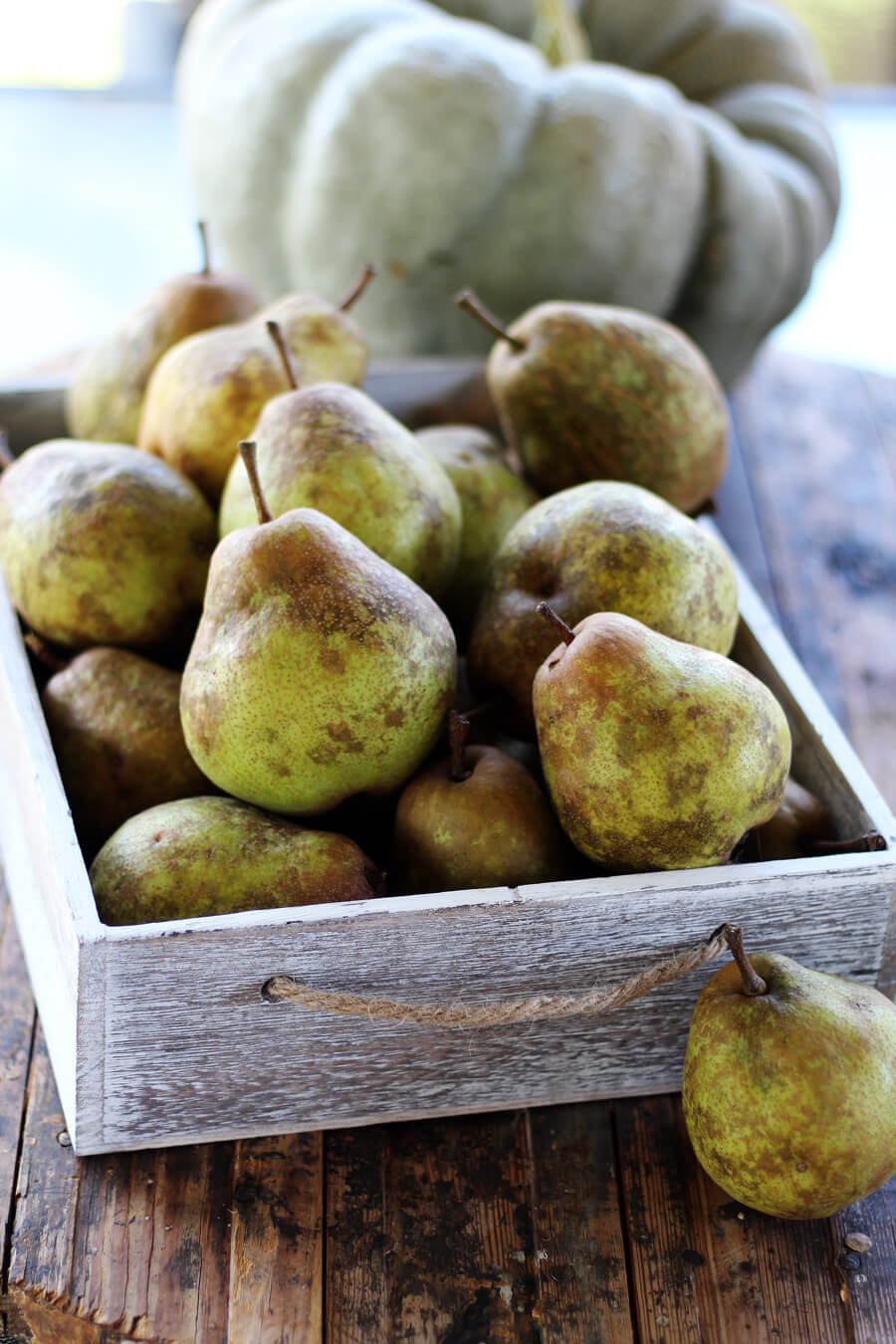 A wooden box filled with fresh pears