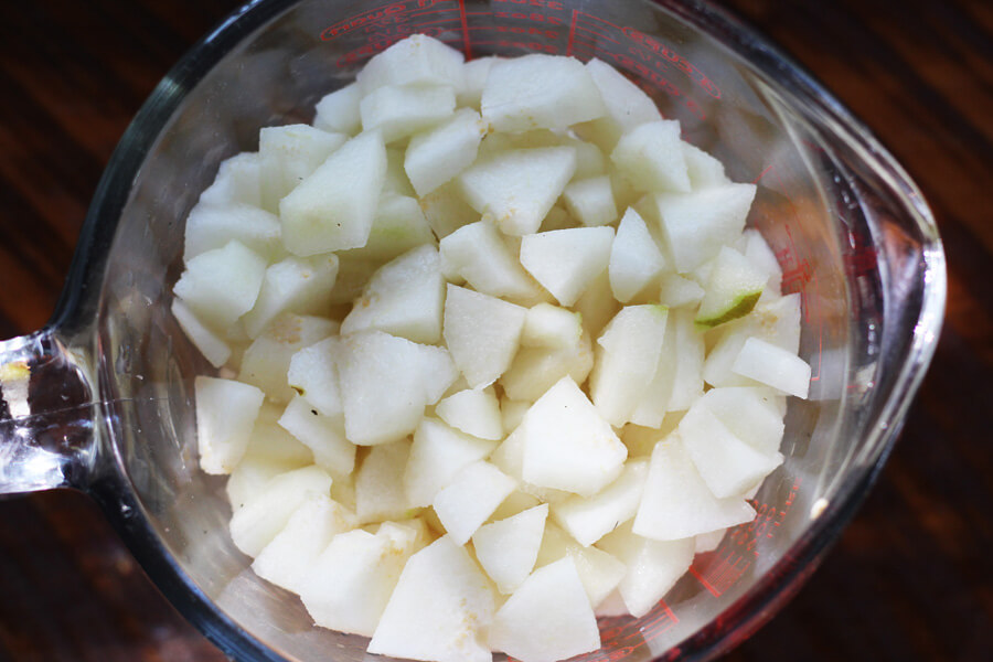 A glass measuring cup full of fresh, chopped pears for making homemade pear preserves.