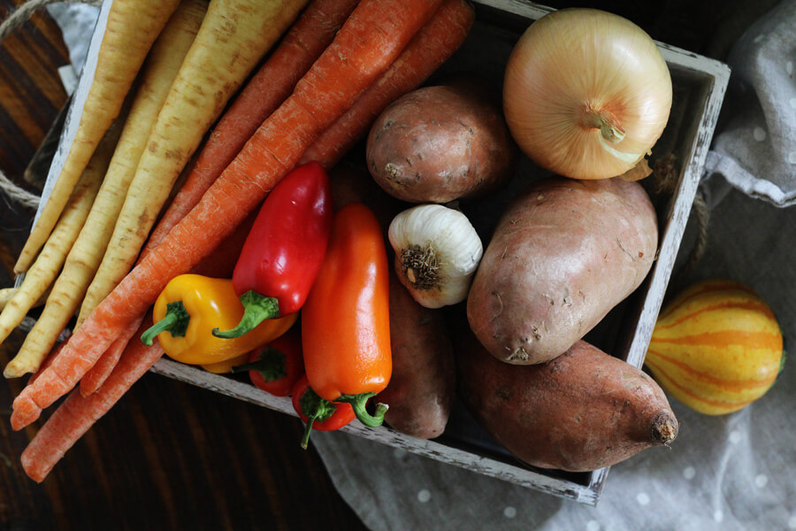 A box full of vegetables, including fresh parsnips, carrots, sweet peppers, onion, garlic and sweet potatoes