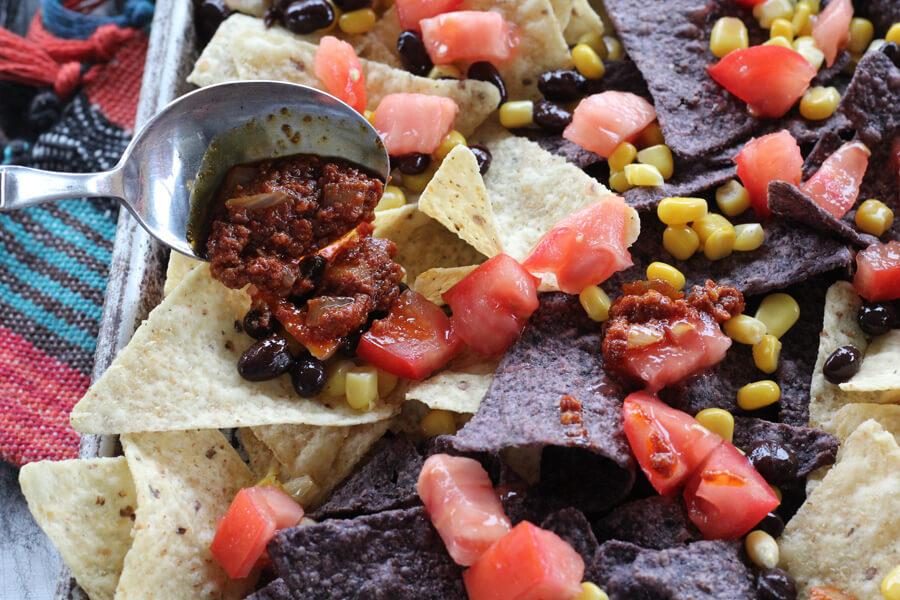 This nachos recipe is loaded with spicy beef chorizo, black beans, corn, and fresh tomatoes.