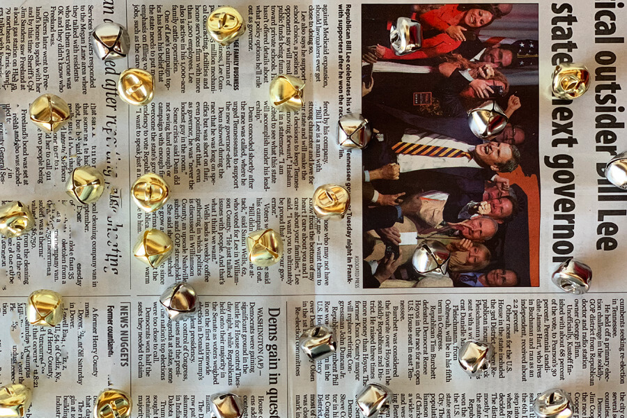 silver and gold jingle bells on a newspaper