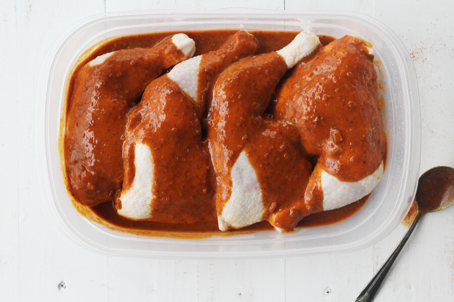 Chicken quarters marinating in barbecue sauce