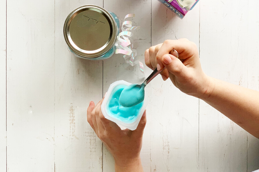 Blue Magic Unicorn Pudding Snack Pack being eaten with a spoon