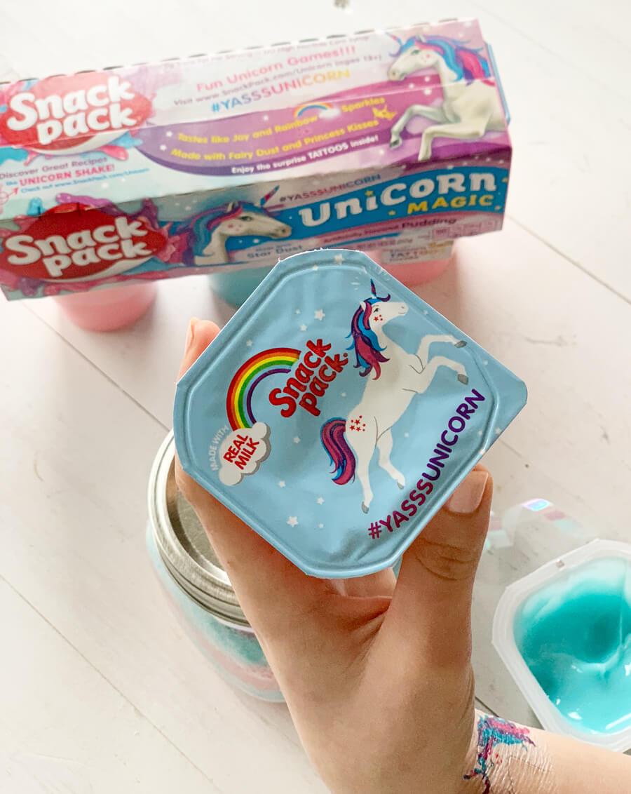 A girl's hand holding a pudding snack pack