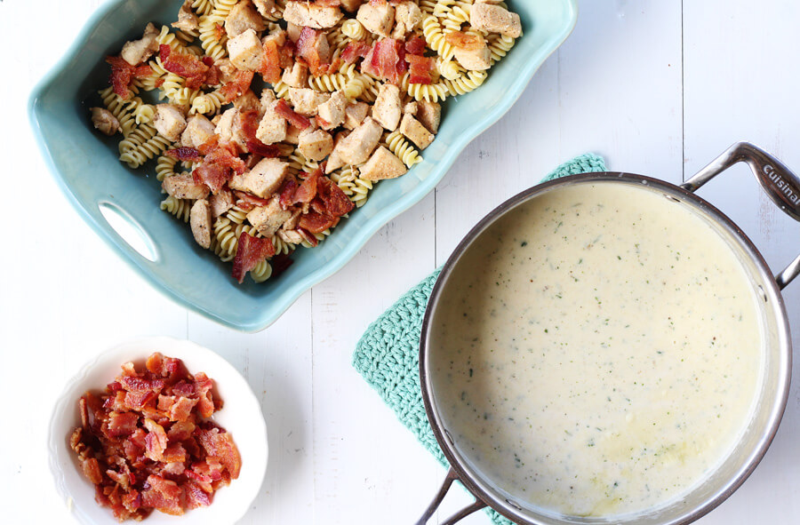 Overhead shot of ingredients for Chicken Bacon Ranch Casserole including a sauce pan of homemade ranch white sauce.