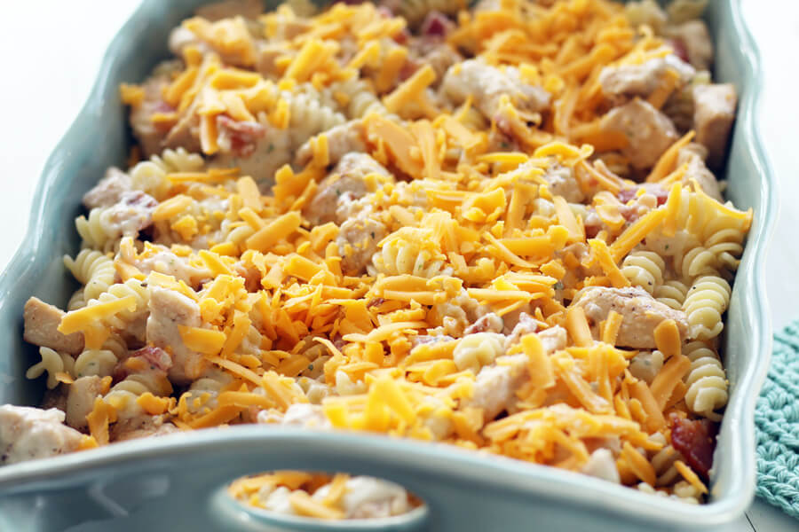 Layers of pasta, chicken, bacon and cheese in a casserole dish.