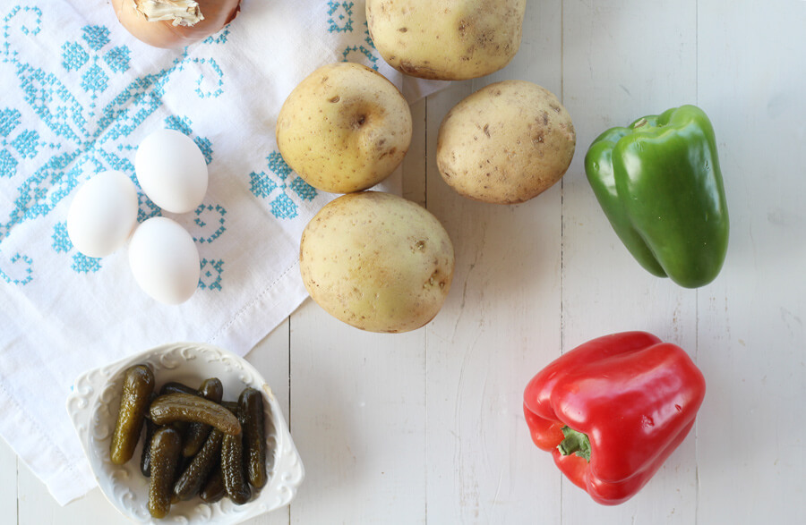 overhead shot of potatoes, sweet pickles, bell peppers, and onion on a white wooden board
