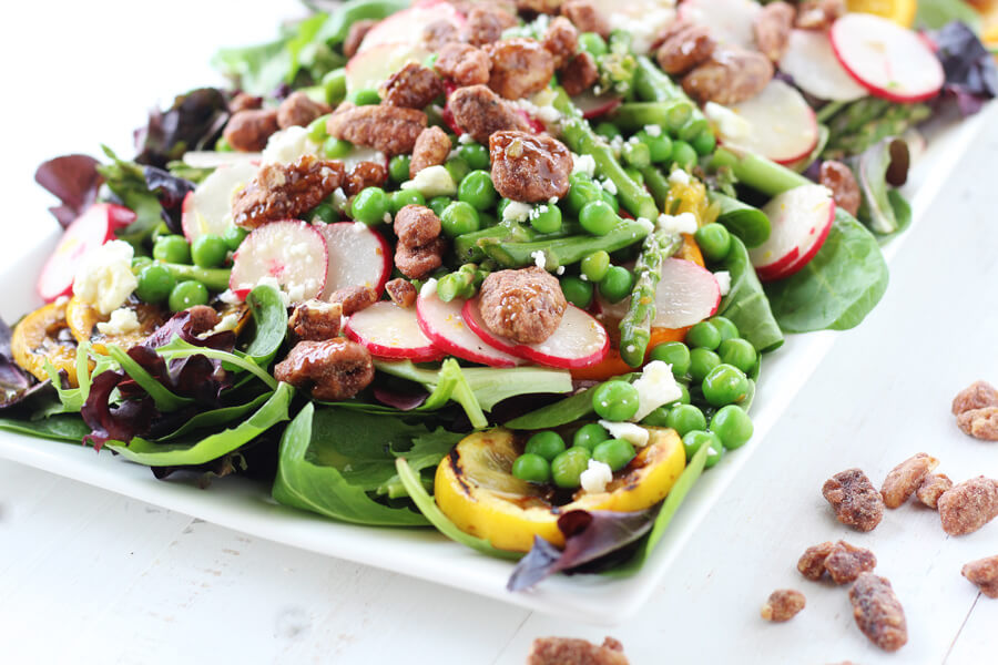 A large tossed salad with spring greens, asparagus, green peas, radishes and more