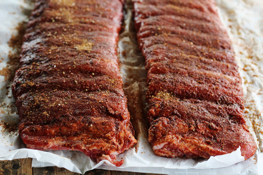 Two racks of St. Louis style pork ribs generously coated with homemade spice rub