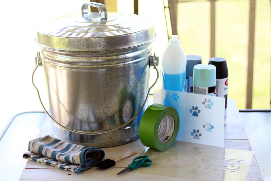 A galvanized metal bucket with a lid, dishwashing detergent, painter's tape, spray paint, stencils and more.