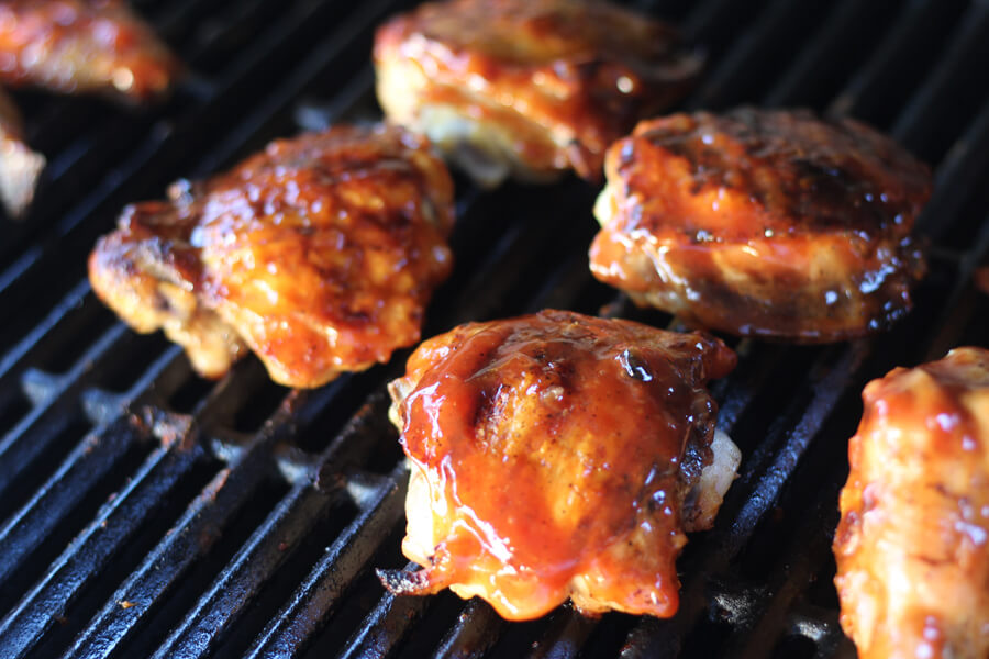 Chicken thighs on a gas grill basted with bbq sauce.