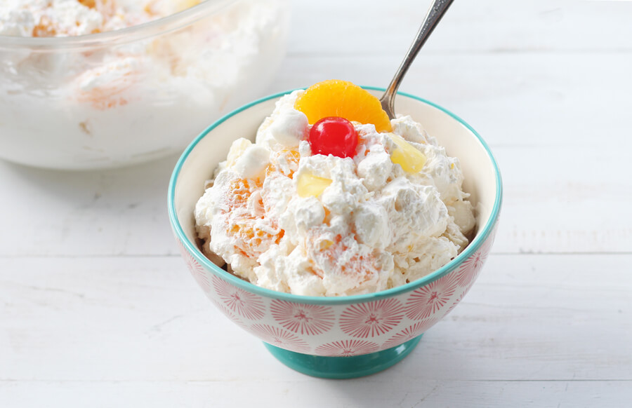 A pretty serving bowl filled with ambrosia salad.