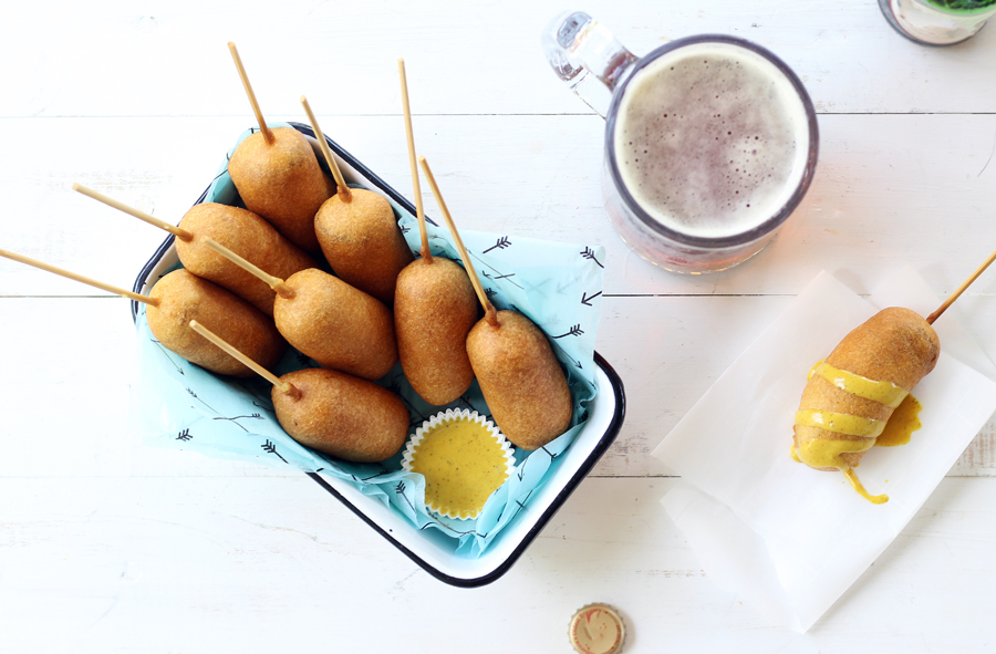 Beer battered bratwurst corn dogs served with a mug of ice cold beer and homemade honey mustard dipping sauce.