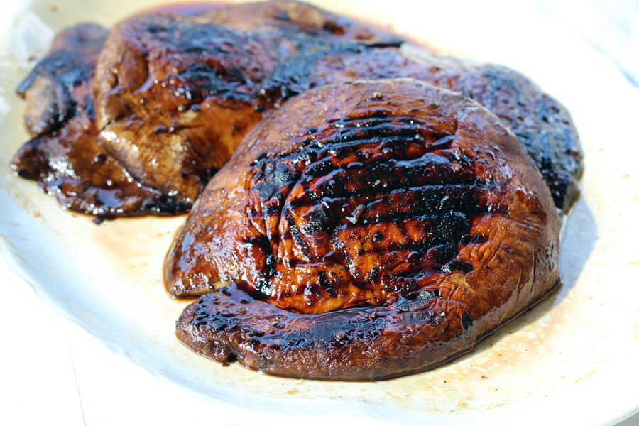 A white platter with grilled, browned portabella mushrooms