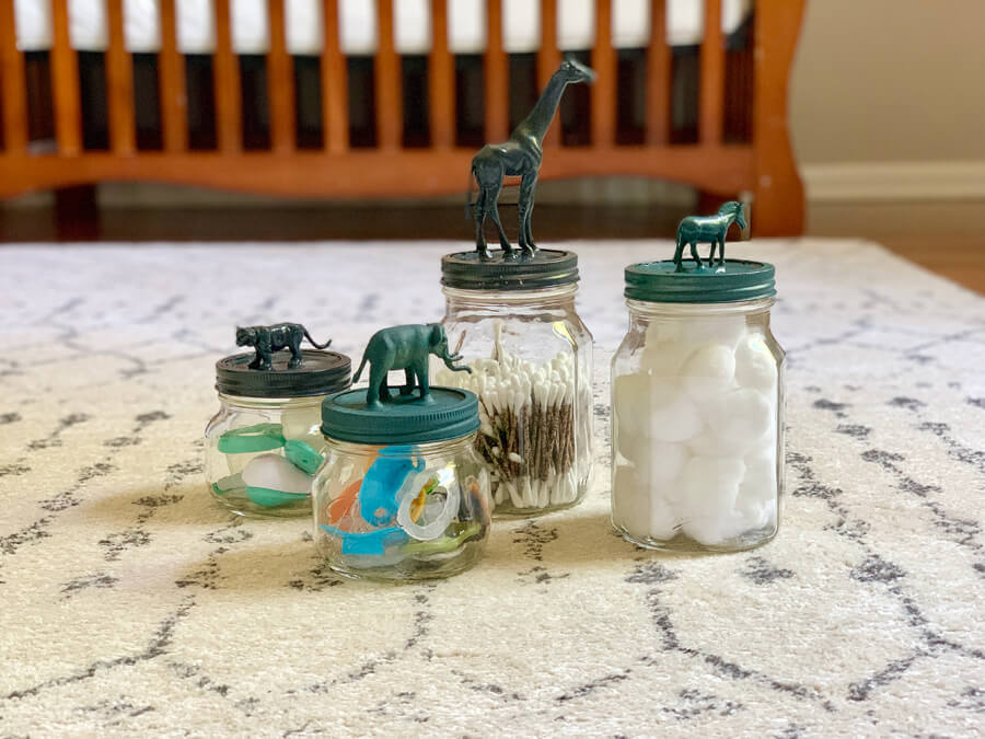 Four mason jars painted in coordinated colors with safari animals on the top