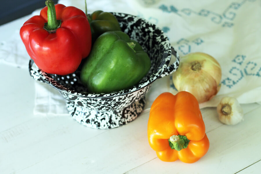 A small colander with multiple colored bell peppers