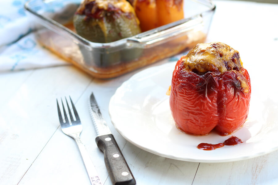 A white plate with a bell pepper stuffed with beef and topped with BBQ sauce and melted cheese.