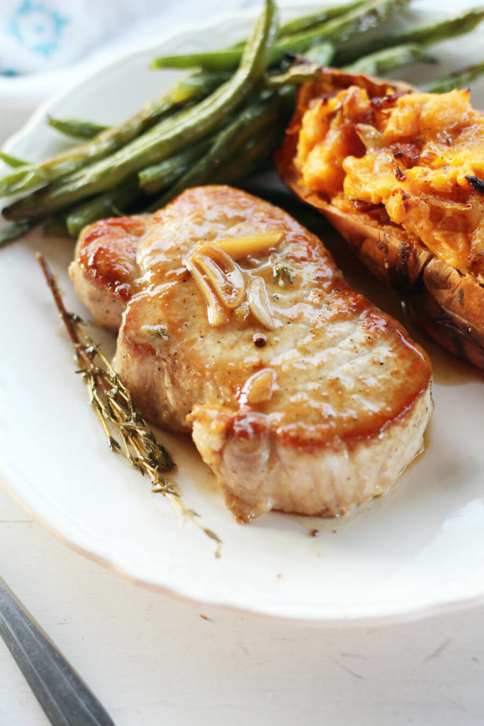 A dinner plate with a pork chop covered in sauce seasoned with garlic, butter and thyme.
