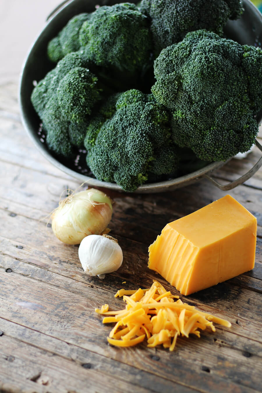 heads of fresh broccoli in a colander next to onion, garlic, and cheddar cheese
