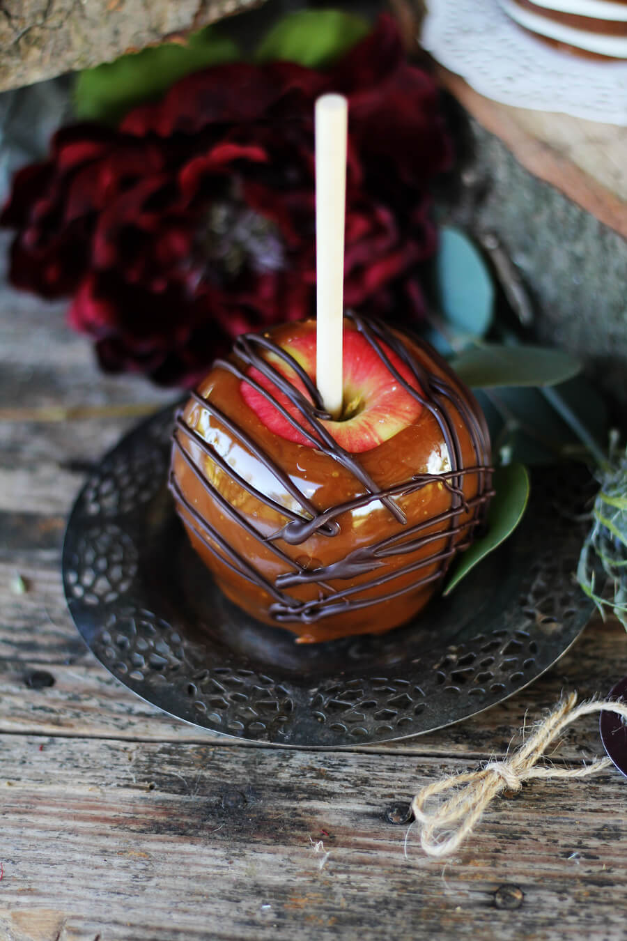 A caramel-coated apple drizzled with dark chocolate, served on a vintage silver tray with ruby red flowers in the background
