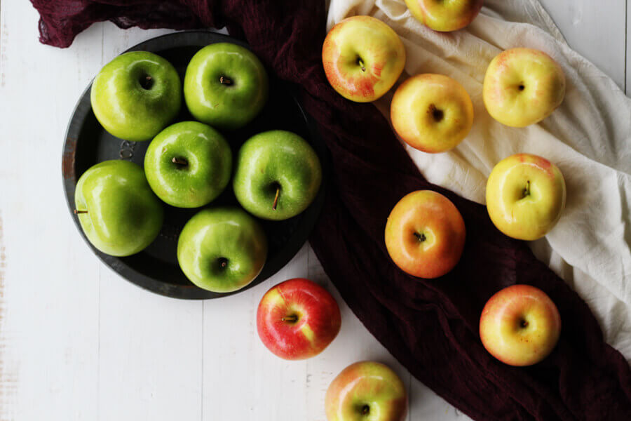 A variety of apples on a white wooden table