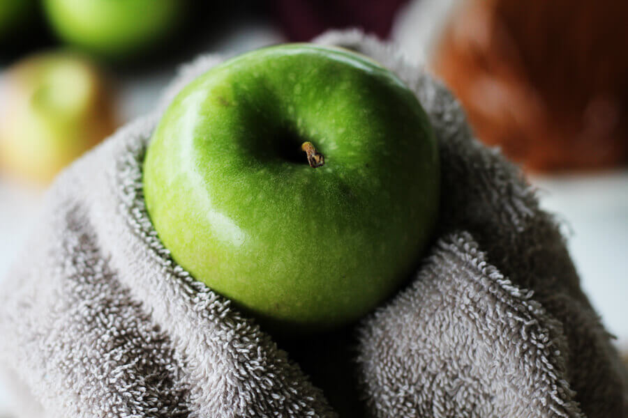 A bright green Granny Smith apple being washed and scrubbed.