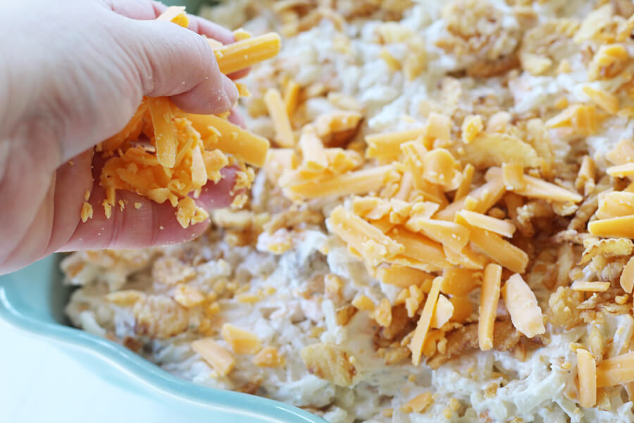 A woman's hand sprinkling shredded cheddar cheese on a dish of hashbrown potatoes.